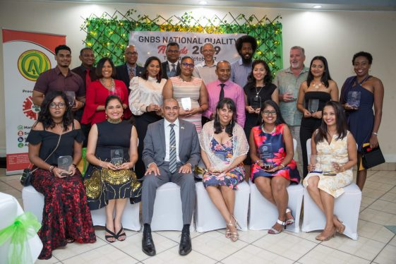 Minister of Business, Hon. Haimraj Rajkumar [seated third left] Director of Manufacturing and Marketing of the Ministry of Business, Dominic Gaskin [third right, back row] and Chairman of the National Standards Council, Rowen Willabus [second right, back row] along with the Prize Winners.