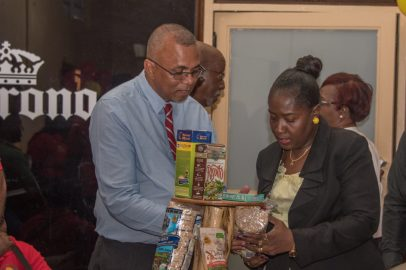 General Manager of Guyana Rice Development Board, Nizam Hassan shows Minister within the Ministry of Agriculture, Hon. Valerie Adams-Yearwood, various products made from blended flour.