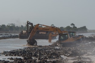 Excavators removing mud from Bellamy Canal to build a wall behind existing boulders along the foreshore in Mahaicony.