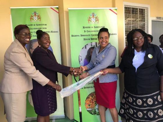 Minister within the Ministry of Agriculture, with responsibility for Rural Affairs, Hon. Valerie Adams-Yearwood and Permanent Secretary of the Ministry of Agriculture, Delma Nedd presenting farming tools to the Demerara-Mahaica, Regional Executive Officer (REO) of Region Four, Pauline Lucas and Chairman Genevieve Allen.