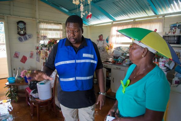 Senior Response Officer of the Civil Defence Commission (CDC), Captain Salim October interacting with Anika Bissoon, a resident of High Dam in her home