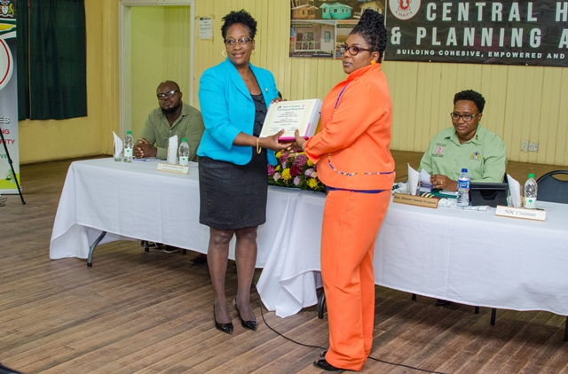 The instruments for 13 areas being handed over to the NDC Chairman, Maureen Philadelphia by Chief Executive Officer (ag) of the Central Housing and Planning Authority (CH&PA), Denise King-Tudor at the of Golden Grove/Haslington Community Centre.