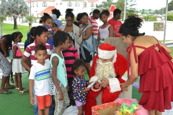 Santa Clause distributing gifts to children at the Christmas Tree light up