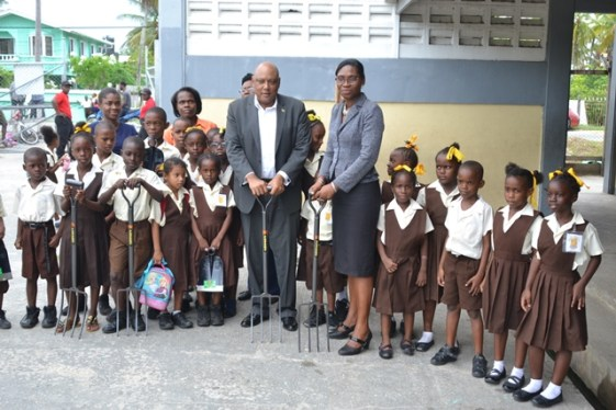 Minister of Natural Resources, Hon. Raphael Trotman handing over the farming tools to Headteacher of the Buxton/Friendship Primary School Yulanda Adams-Blair, flanked by students of the school.