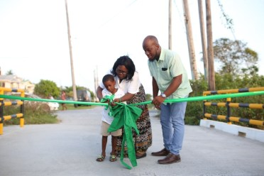 The ceremonial cutting of the ribbon for the bridge linking Roxanne Burnham Gardens to Rasville by Denroy Tudor, Councilor of Constituency 14, Constituency 14's Manager Brenda Williams and young boy from the community