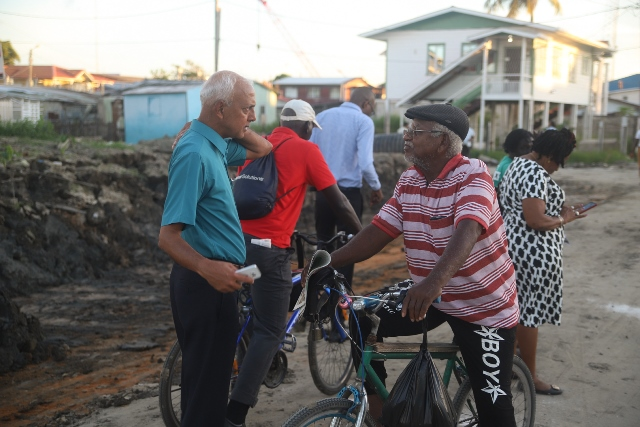 Minister of Communities, Hon. Ronald Bulkan listening to one of the concerns of a resident of Alexander Village.