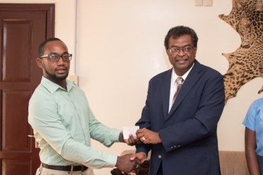 Minister of Public Security Khemraj Ramjattan hand over a cheque to Kennard Browne Physical Education and Visual Arts teacher at Diamond Secondary School.