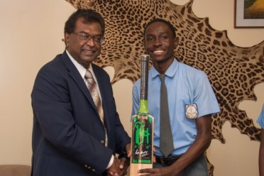 Minister of Public Security Khemraj Ramjattan presents one of the cricket bats to Diamond Secondary School student Yuhane Porter