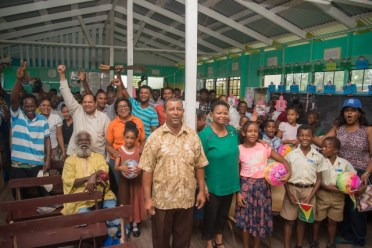 Prime Minister, Hon. Moses Nagamootoo, Minister of Public Health, Hon. Volda Lawrence and Minister of Public Telecommunications, Hon. Catherine Hughes with residents of Aliki .