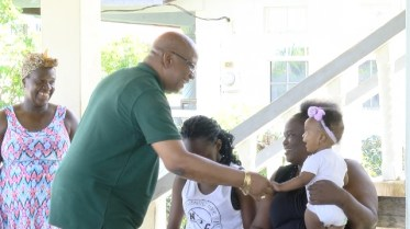 Minister of Finance, Hon. Winston Jordan greeting a family during a Richmond Village community meeting, in Essequibo.