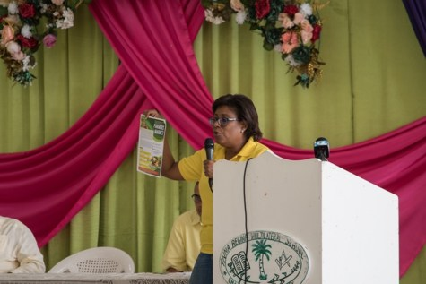 Minister of Public Telecommunications, Hon. Catherine Hughes holds up a flyer advertising the Farmers Market which can be accessed via an app.