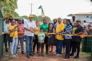 Minister of Natural Resources, the Hon. Raphael Trotman gather with residents of Lethem to cut the ribbon to the newly Restored Cashew Grove Park.