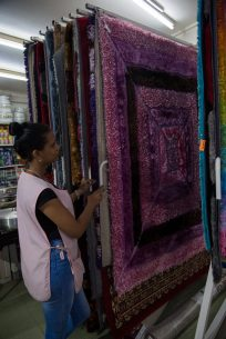 An assistant displaying the wide choice in carpets