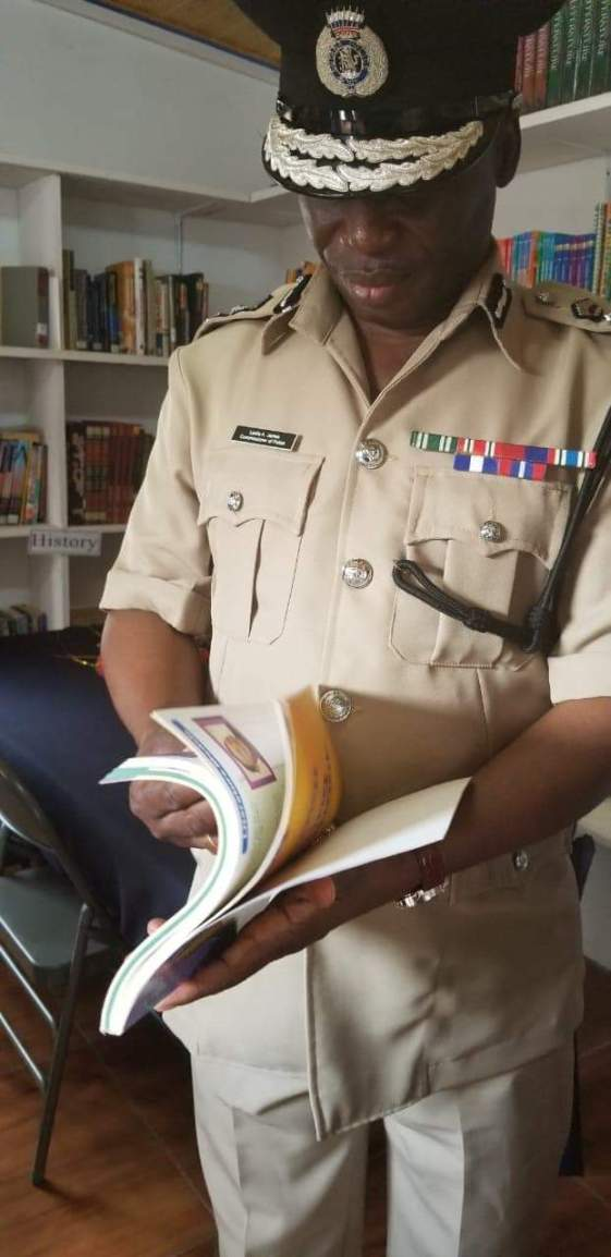 Commissioner of Police Leslie James checking out a book from the Reading and Research Library