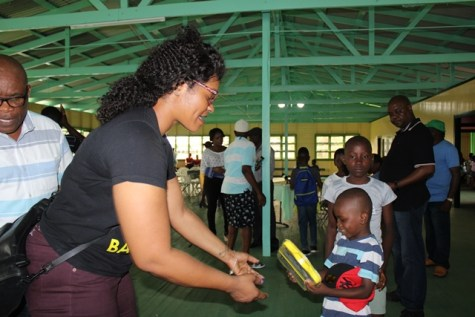 A member of the Ministry of Social Protection team helps to share gifts to the little ones