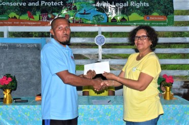 Minister within the Ministry of Indigenous People's Affairs Valerie Garrido-Lowe presenting the cheques to some of the Santa Cruz farmers