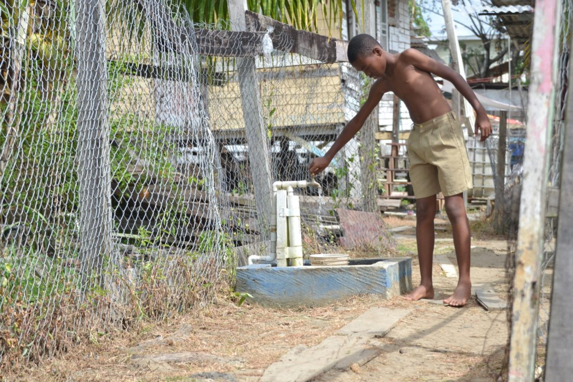 A young resident of D' Urban Backlands, Burnham Drive Annex turns on the tap in his yard