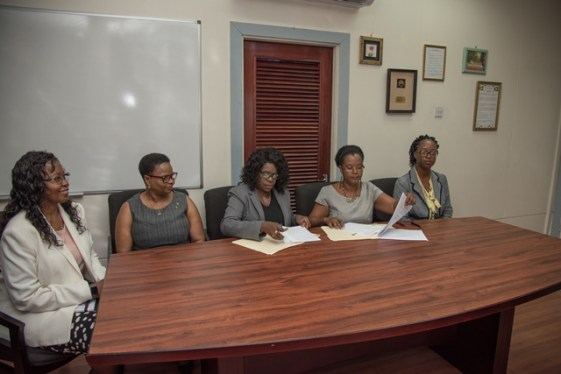 Ministry of Public Health's Permanent Secretary, Collette Adams and Simone Sills, Executive Director of the National Coordinating Coalition of NGOs signs the agreement to initiate the work. Looking on are (from left to right) Finance Director, Health Sector Development Unit, MoPH Sonia Roberts, Minister of Public Health Volda Lawrence and Tekia Hanover, Administrative Officer of the Country Coordinating Mechanism, Global Fund.