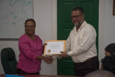 Chief Labour Officer, Charles Ogle presenting a certificate to one of the participants.