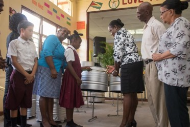 Minister of Education Dr Nicolette Henry is assisted by a student to cut the ribbon before handing over the steel pans to the students and teachers of Kwakwani Secondary School.