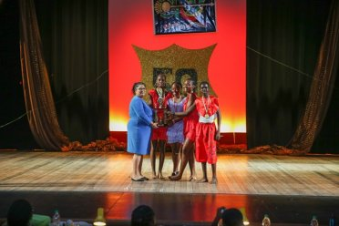 Charlestown Secondary Masqueraders receive their trophies all smiles from Principal Education Officer, Volaika Jaikishun.