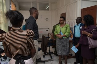 Minister Lawrence being briefed by Head of Vector Control Services, Dr. Horace Cox while she walked through the department.