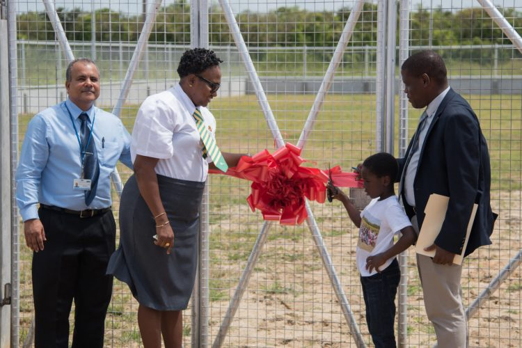 Minister within the Ministry of Communities with responsibility for Housing the Hon. Annette Ferguson, Chief Executive Officer to CHPA Lelon Saul, Chief Executive Officer to Food for the Poor Kent Vincent looks on a child cuts the ribbon to commission the play ground