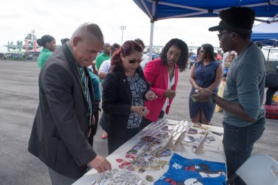 Minister of Social Cohesion Dr. George Norton, Minister of State Dawn Hasting, Permanent Secretary attached to the Social Cohesion department Melissa Tucker viewing the products offered by Jamal Farley, owner of Farley's Digital Arts Plus.