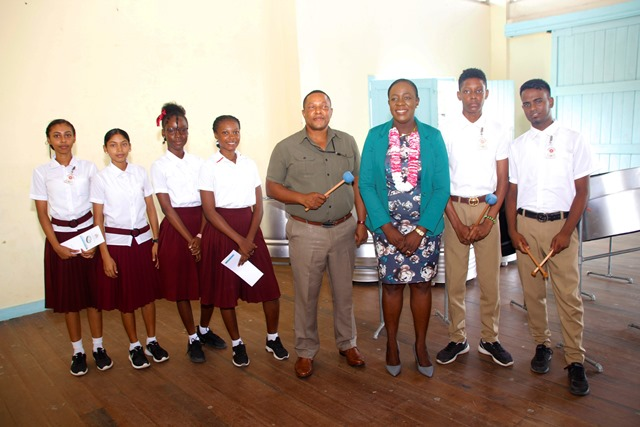 Minister Henry and the Headteacher of the Skeldon High School pose with students of the school with their newly acquired steelpans.