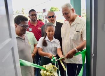 Minister of Agriculture Hon. Noel Holder (right) and CEO of the National Drainage and Irrigation Authority (NDIA) Frederick Flatts assist a Cotton Field Secondary School student to cut the ribbon to officially commission the new NDIA office.