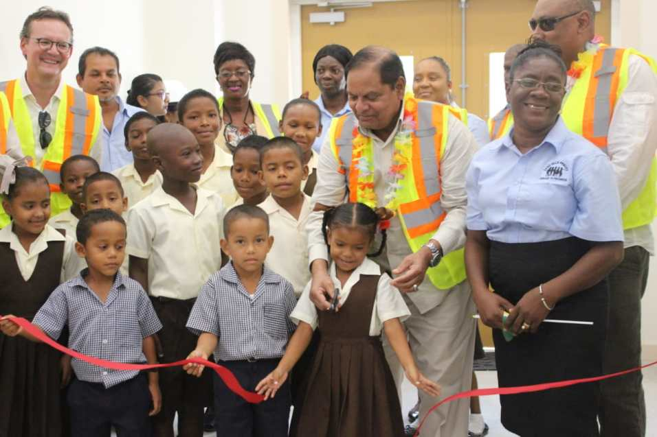 Prime Minister Hon. Moses Nagamootoo is assisted in cutting the ribbon to commission the new sand Hill Primary school by several students