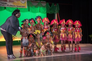 Tapakuma Primary Dancers receiving the Second-place trophy for the 8-10 Dance Category from a Ministry of Education Representative (left).
