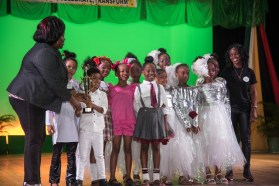 Westfield Prep Dancers (center) and Teacher (right) receive their First-place award from a Ministry of Education Representative (left) in the 8-10 Dance Category.