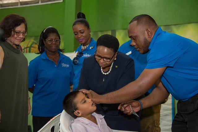 Minister of Public Health, Hon. Volda Lawrence, assists with placing a hearing aid into the ear of 8-year-old Thalesh Singh. Looking on is First Lady, Mrs. Sandra Granger, (first from left) and Dr. Ruth Queicoe, Audiological Physician (second from left) and other Ministry staff.