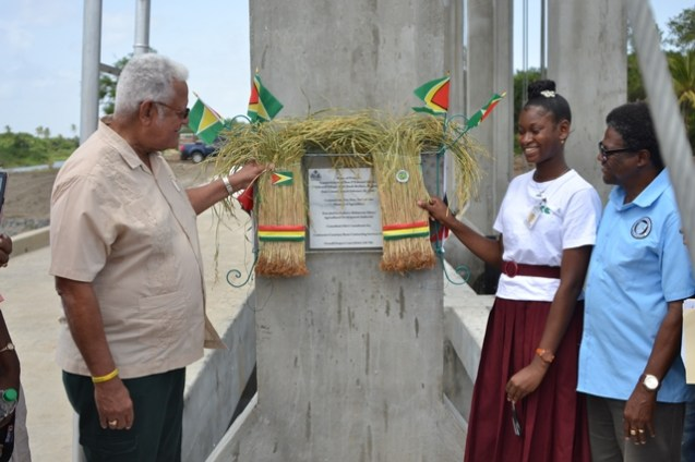 Minister of Agriculture Noel Holder along with Chief Executive Officer of NDIA Frederick Flatts and a student of Rosignol Secondary Commissions the Sluice at D'Edward.
