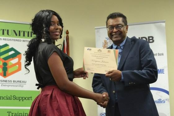 Kerryann Johnson receiving her certificate from Minister of Public Security, Khemraj Ramjattan.
