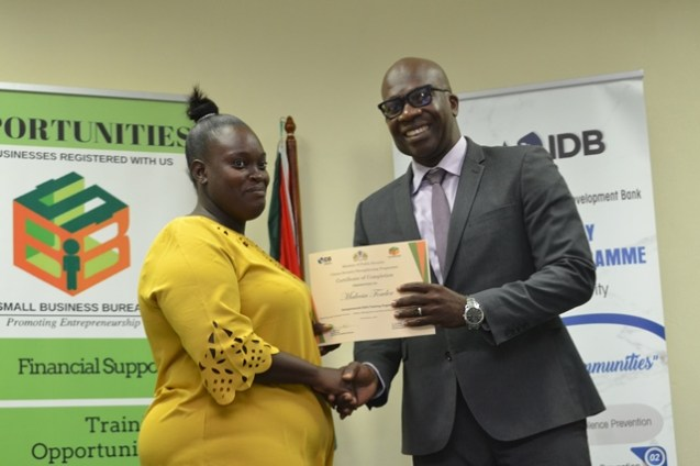 Coordinator of CSSP Dr. Clement Henry handing out certificates to youths who recently completed an entrepreneurship programme.