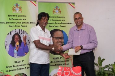 Region 9, third prize winner, Panchan Singh receives his prize from GRDB Managing Director, Nizam Hassan.
