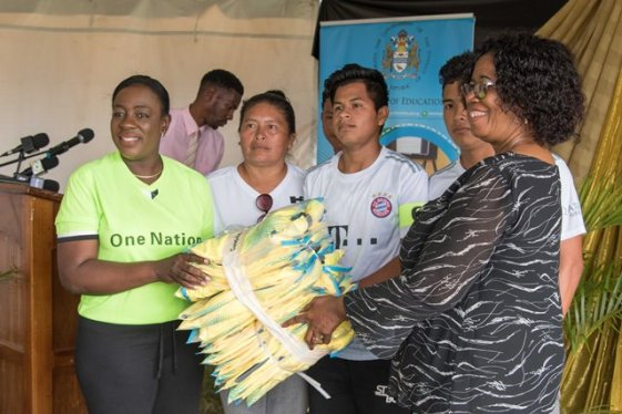 Minister of Education Dr. Nicolette Henry handing over the sports gear to students of Desrey Fox Secondary along with Administrator (ag) of the Unit of Allied Arts Lorraine Barker-King.