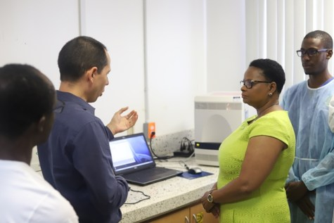 Virologist (in blue) Dr. Lionel Gresh explains to the Public Health Minister Volda Lawrence.