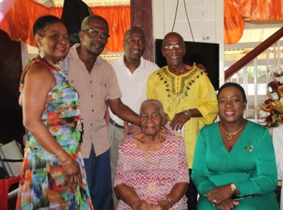 Mrs. Gravesande surrounded by three of her sons, her daughter-in-law and Minister Henry.