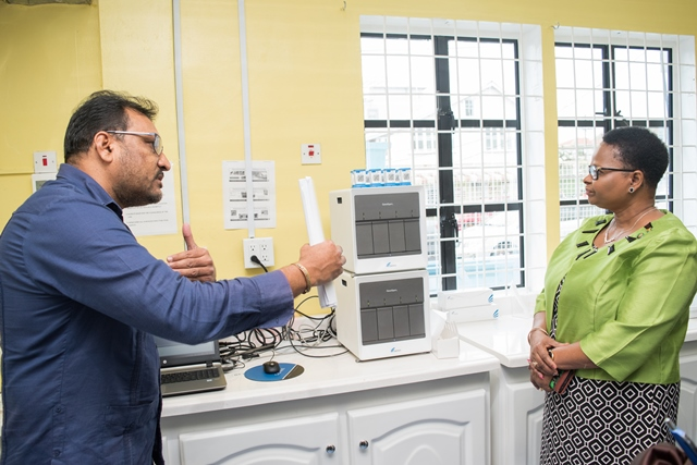 National Tuberculosis Programme Coordinator, Dr. Jeetendra Mohanlall speaks with Minister of Public Health, Volda Lawrence during a brief visit to the laboratory.