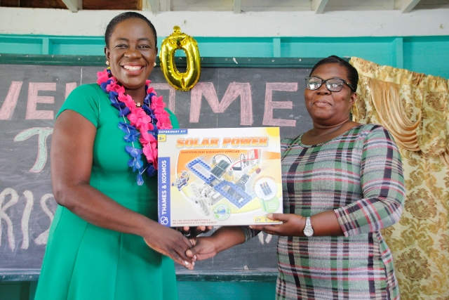 Minister Henry handing-over one of the kits to a teacher of the Fyrish Primary School.