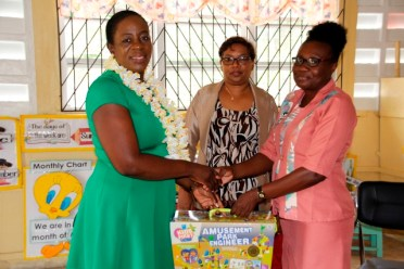 Minister Henry handing-over kits to the Head Teacher of the Hibiscus Nursery School.