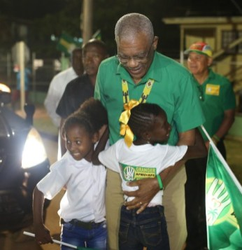 HE President David Granger is warmly greet by two little girls as he makes his way to the stage.