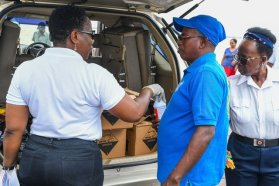 Director General of the Maritime Administration Department, Claudette Rogers distributes cleaning supplies to boating operators at Parika Stelling