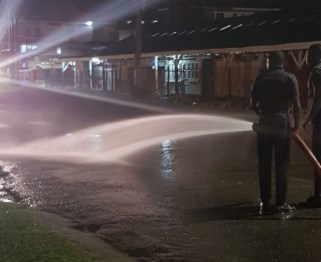 Members of the Guyana Fire Service washing down a section of Regent Street outside of Bourda Market.