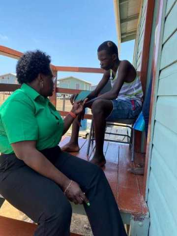 Minister Broomes interacts with Reon Mobb who suffered a severe head injury.