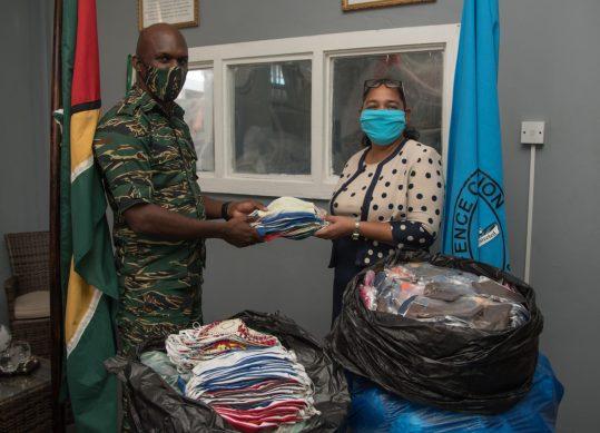 Lt. Col. Kester Craig handing over face masks to GPOC's Deputy Post Master General, Anastasia Jessemy-Lynch