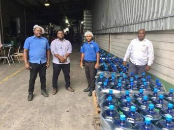 DDL Staff with some of the bottles of alcohol-based sanitising cleaner donated to the Ministry of Public Health (MoPH)